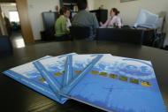 fotos de unos folletos de empresas encima de una mesa
