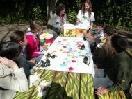 foto de una mesa alargada con niños haciendo trabajos manuales