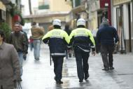 Foto de espaldas de dos Policías Locales caminando por la calle